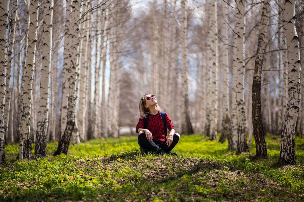Frau sitzt in Baumgruppe und schaut nach oben